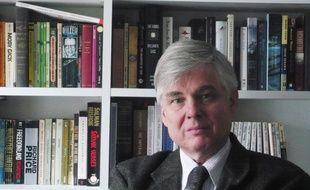 Bernard Genton dans bureau, devant de nombreux ouvrages, en langue anglaise.