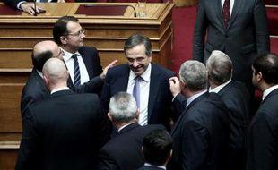 Le Premier ministre grec Antonis Samaras (c) congratulé par des députés au Parlement grec à Athènes après l'adoption du budget 2015, le 7 décembre 2014