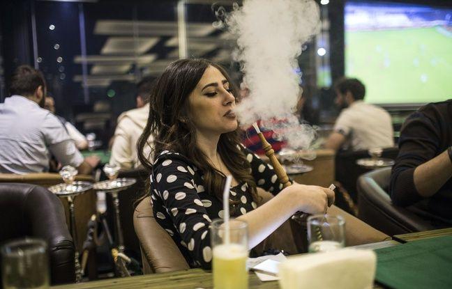 En Syrie, une jeune femme fumant le narguilé.