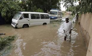 Un homme les pieds dans l'eau dans une ville au sud de Khartoum (Soudan) pendant les inondations de l'été 2020.