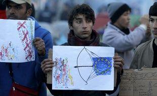 Des migrants brandissent des dessins alors que l'UE et la Turquie sont en négociation  à Bruxelles à propos des migrants, le 18 mars 2016 à la frontière macédo-grecque Idomeni.