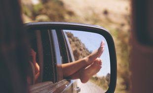 Illustration d'une personne sortant les pieds par la fenêtre d'une voiture