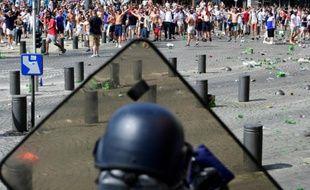 Un poilcier derrière son bouclier face à des supporteurs anglais lors de heurts, le 11 juin 2016 à Marseille