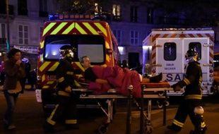 Une victime des attaques de Paris évacuée par des pompiers, le 13 novembre 2015