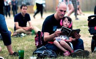 Aux Solidays 2015, un père et sa fille choisissent leur prochain concert dans le guide du festival.