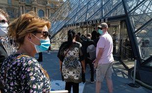 Une femme porte un masque avant d'entrer dans le musée du Louvre