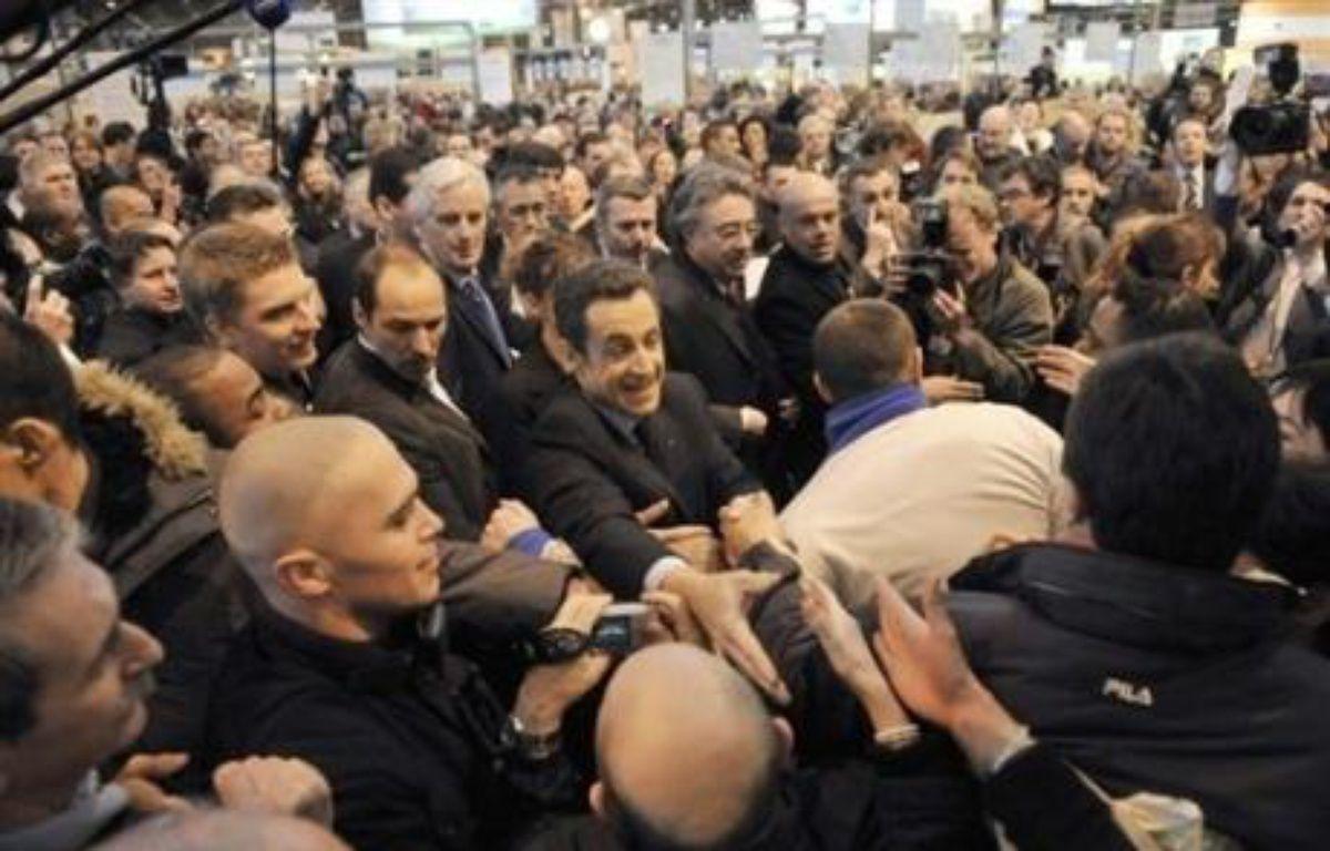 Après son discours, Nicolas Sarkozy a satisfait à la tradition en parcourant au pas de charge et dans une cohue indescriptible les allées du salon, le temps d'engloutir un verre de lait, une tranche de jambon et une pomme. Souvent applaudi à son passage, il a aussi essuyé quelques sifflets. – Eric Feferberg AFP