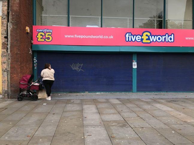 Une jeune mère devant une boutique fermée du centre ville de Romford, le 20 octobre 2019.