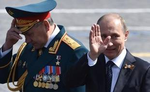 Le président russe Vladimir Poutine (d) et le ministre de la Défense Serguei Shoïgou quittent la place Rouge à Moscou après la parade militaire, le 9 mai 2015