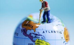 Une figurine plante un marteau piqueur dans un globe terrestre (image d'illustration).