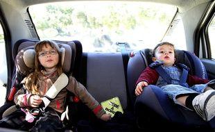 : Enfants attaches dans un siège auto pour la sécurité en voiture.