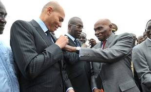 Dakar (Sénégal), le 19 janvier 2011. Abdulaye Wade, président du Sénégal, ajuste un ruban aux couleurs de son pays sur le costume de son fils, Karim.
