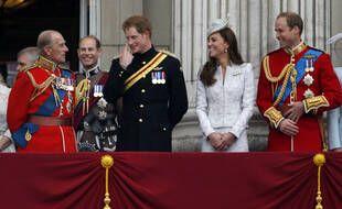 Sur cette photo datant de 2014, le prince Harry, rit avec son grand-père le prince Philip, Kate, et le prince William au balcon de Buckingham Palace.
