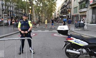 Un policier espagnol sur les Ramblas, vendredi 18 août, au lendemain d'un attentat qui a ensanglanté l'avenue la plus touristique de Barcelone. L'avenue a rouvert vendredi matin, mais reste fermée aux véhicules et très surveillée.