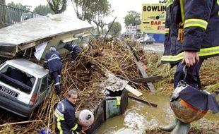 Des sapeurs-pompiers s'affairent autour des voitures et du mobil-home enchevêtrés près d'un pont, à Saint-Pons-les-Mures le 19 septembre 2009, après avoir été emportés par un cours d'eau en crue. Le sud de la France a été touché la veille par de violents orages et des précipitations intenses entraînant débordements de rivières et coulées de boues qui ont fait quelques blessés légers mais provoqué de sérieuses perturbations dans les transports. La ville de Sainte-Maxime a été envahie par les eaux pendant quelques heures.
