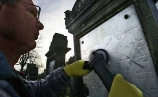 Un homme tente d'effacer des inscriptions nazis sur une tombe, illustration