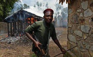 Un soldat sort d'une maison incendiée par des opposants le 5 juin 2015 à Mugongomanga, près de Bujumbura