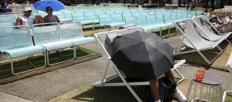 Des spectateurs se protègent du soleil pendant l'Open de tennis d'Australie à Melbourne le 25 janvier 2019.