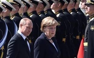 La chancelière allemande Angela Merkel et le président russe Vladimir Poutine passent les troupes en revue le 10 mai 2015 à Moscou