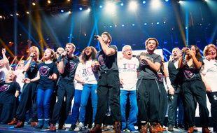 Les chanteurs avec les bénévoles, pendant le spectacle des Enfoirés, diffusé vendredi soir sur TF1.