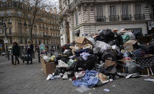 Des piétons devant une montagne de déchets dans les rues de Marseille le 23 décembre 2020, alors que les éboueurs sont en grève. (Photo by Christophe SIMON / AFP)
