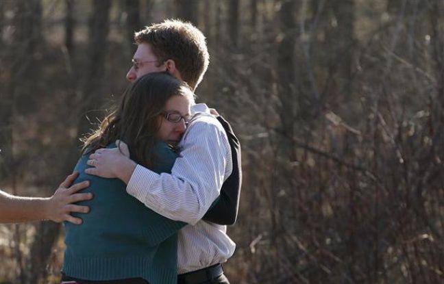 Un homme et une femme réagissent après qu'une fusillade a éclaté dans une école primaire deNewton (Connecticut), le 14 décembre 2012.
