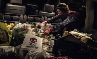 """Un membre du mouvement les """"Gars'pilleurs"""" charge un camion avec de la nourriture récoltée dans les poubelles d'un supermarché au sud de Lyon, le 24 septembre 2015"""