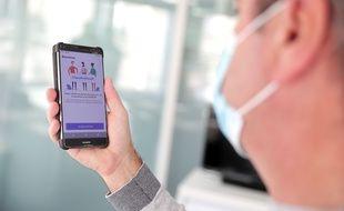 Un homme masqué regarde son téléphone, et là, oui, l'application TousAntiCovid apparaît.