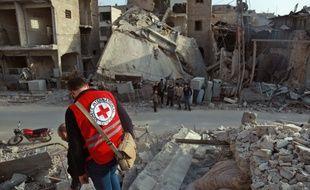 Un volontaire de la Croix Rouge franchit des gravas à Douma, dans la Ghouta orientale, le 5 mars.