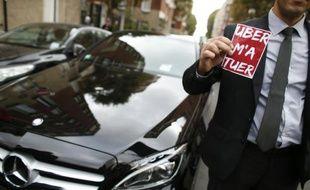 """Un chauffeur Uber manifeste à Paris, montrant un autocollant déplorant """"Uber m'a tuer"""", le 13 octobre 2015 à Paris"""