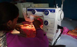 Une femme coud grâce à une machine alimentée à l'électricité solaire, en Inde.