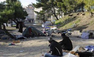 Des personnes  sont assises sur un matelas, le 2 décembre 2010, dans le quartier de la porte  d'Aix à Marseille, où plusieurs familles roms se sont installées depuis quelques  semaines faute de logement.