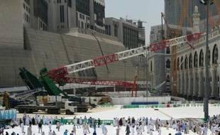Des pélerins passent devant la grue qui s'est effondrée quelques jours plus tôt à la Grande mosquée de la Mecque, le 12 septembre 2015