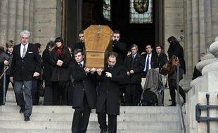 Des employés des pompes funèbres portent le cercueil de Bernard Mazières, ancien journaliste politique du Parisien assassiné fin décembre, à l'issue de la cérémonie des obsèques, le 14 janvier 2011, en l'église Saint-Sulpice à Paris.