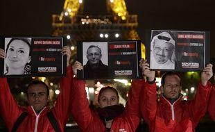 Des gens tenant des portraits de journalistes tués devant la Tour Eiffel, jeudi soir.
