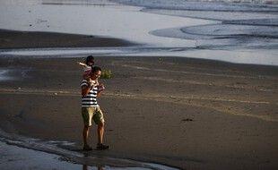 Un père et son enfant sur la plage (image d'illustration).