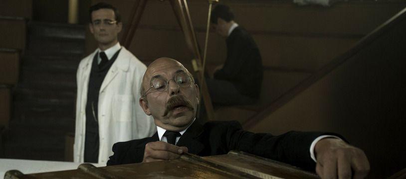 Alphonse Bertillon (Christian Hecq) examine une malle dans laquelle se trouve le corps d'une inconnue