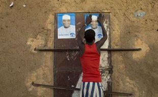 Un jeune Malien colle une affiche de campagne pour le candidat Ibrahim Boubacar Keita  à Gao, au Nord du Mali,  le 25 juillet 2013.