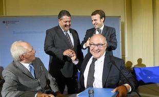 (g à d): le ministre allemand des Finances Wolfgang Schaeuble et son homologue de l'Economie Sigmar Gabriel avec le ministre francais de l'Economie Emmanuel Macron et celui des Finances Michel Sapin, à Berlin le 20 octobre 2014