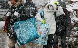 Des survivants repartent vers leur refuge après avoir récupéré quelques affaires parmi les décombres de leurs maisons à Natori dans la préfecture de Miyagi, le 17 mars 2011.