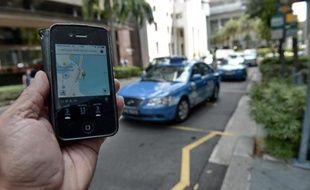 Une personne utilise avec son smartphone l'application Uber, le service américain de voitures avec chauffeur (VTC), le 10 octobre 2014 à Singapour
