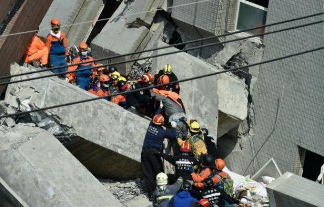 Des secouristes recherchent des survivants dans les décombres d'un immeuble le 7 février 2016, à Tainan, dans le sud de Taïwan, au lendemain d'un séisme de magnitude 6,4