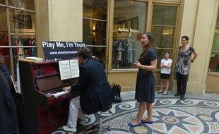 Des passants s'essayant au piano mis à disposition galerie Vivienne à Paris (2e), le 25 juin 2014