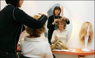 Une femme atteinte d'un cancer du sein essaye un perruque  en février 2009, à Clamart dans les Hauts-de-Seine.