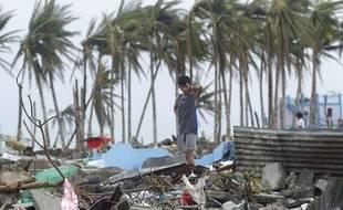 Un jeune homme sur les ruines de sa maison après le passage du typhon Haiyan, à Tacloban, aux Philippines, le 12 novembre 2013.