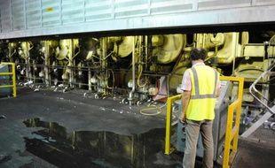 Un employé d'une usine à papier contrôle la ligne de production