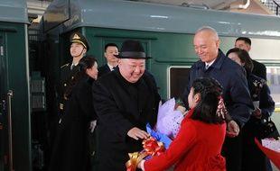 Kim Jong-un reçoit un bouquet de fleurs à son arrivée en train à Pékin, le 8 janvier 2019.