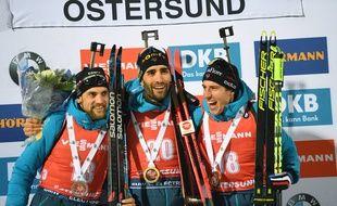 Martin Fourcade entouré de Simon Desthieux et Quentin Fillon Maillet sur le podium de l'individuel d'Ostersund, le 4 décembre 2019.