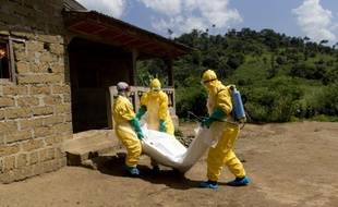 Des membres de la Croix-Rouge portent le corps d'une victime du virus Ebola à Macenta, en Guinée, le 21 novembre 2014