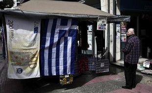 Un drapeau grec et une serviette illustrée d'un billet de 200 euros suspendus à un kiosque à Athènes le 22 mars 2015